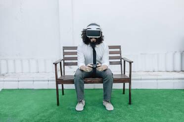 Businessman using virtual reality eyeglasses while playing video game at backyard - MRRF00545
