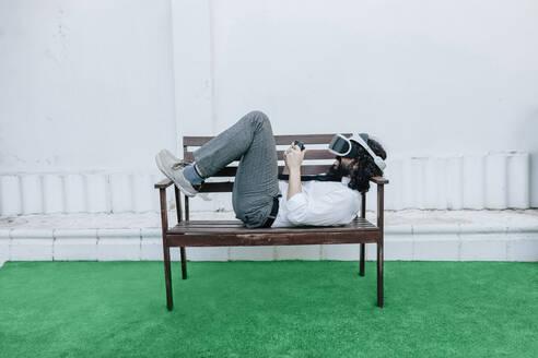 Man wearing virtual reality eyeglasses playing game while lying on bench backyard - MRRF00548
