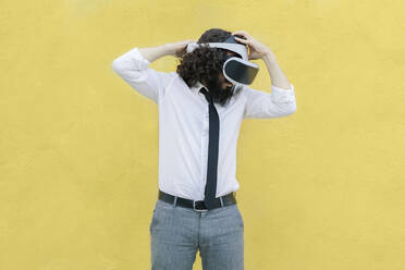 Man adjusting virtual reality eyeglasses while standing against yellow wall - MRRF00551