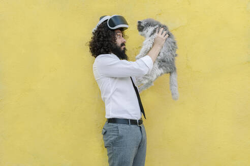 Man with virtual reality eyeglasses on head playing with cat while standing against wall - MRRF00560