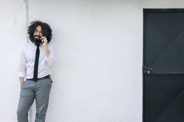Businessman talking on mobile phone while leaning on wall - MRRF00566