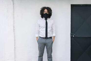 Businessman with protective face mask and hands in pockets standing against wall - MRRF00569
