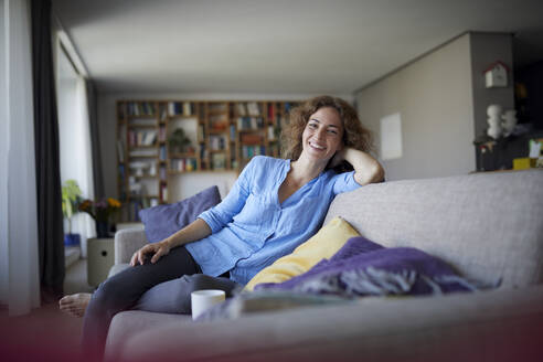 Smiling woman with head in hands sitting on sofa at home - RBF07947