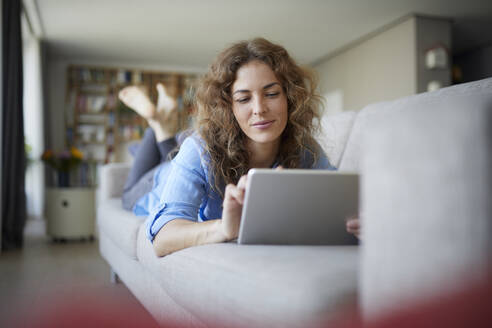 Beautiful woman using digital tablet while lying on sofa at home - RBF07956