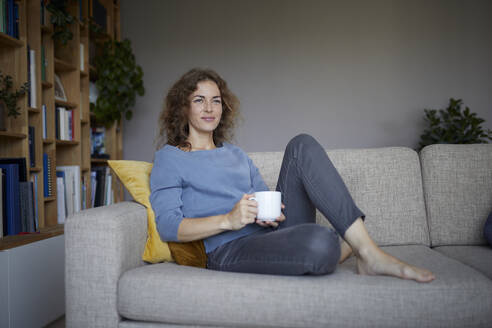 Woman holding coffee cup while sitting on sofa at home - RBF07974