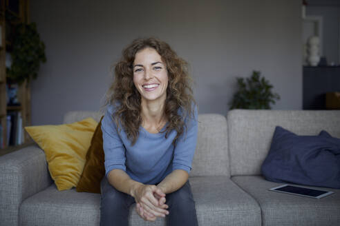 Beautiful woman smiling while sitting on sofa at home - RBF07980
