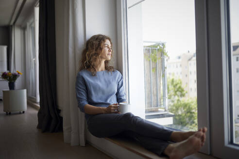 Woman holding coffee cup while sitting on window sill at home - RBF07983
