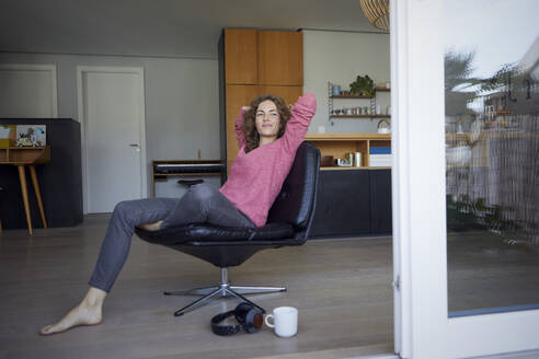 Smiling woman with hands behind head resting on chair at home - RBF08019