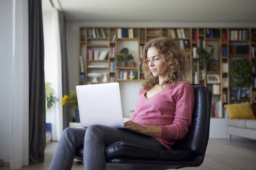 Woman using laptop while sitting on chair at home - RBF08022