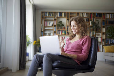 Smiling woman waving hand to video call on laptop while sitting at home - RBF08025