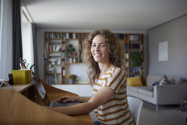 Smiling woman working on laptop while sitting by desk at home - RBF08028