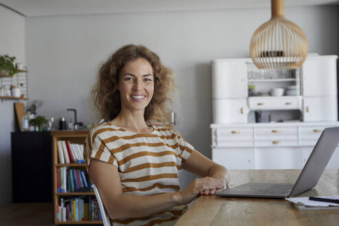 Smiling woman with laptop sitting by table at home - RBF08037