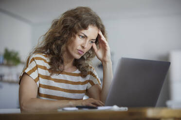Woman sitting with head in hands while working on laptop at home - RBF08040