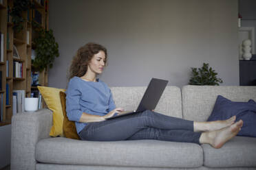Woman working on laptop while sitting on sofa at home - RBF08043