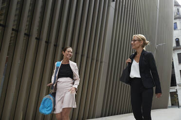 Smiling female colleagues talking while walking by office building in downtown - PMF01288