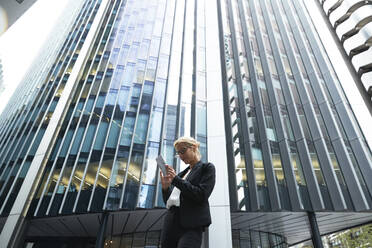 Blond businesswoman using phone while standing against modern office building in financial district of city - PMF01291