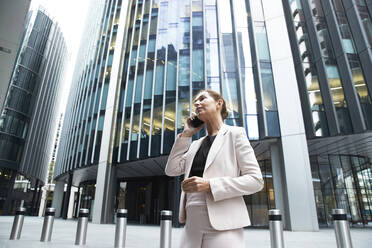 Businesswoman talking on mobile phone while standing against modern office skyscraper in financial district - PMF01297