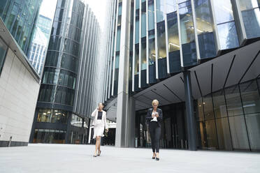 Female entrepreneurs walking with smart phones against office building at downtown district in city - PMF01300