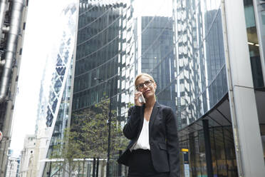 Blond female entrepreneur talking on phone while standing against office building at downtown district - PMF01303
