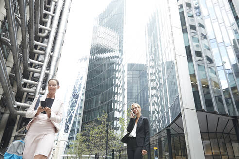 Businesswomen using mobile phones against office buildings in city - PMF01306