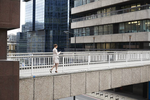 Businesswoman using smart phone while walking on footbridge at downtown district - PMF01309