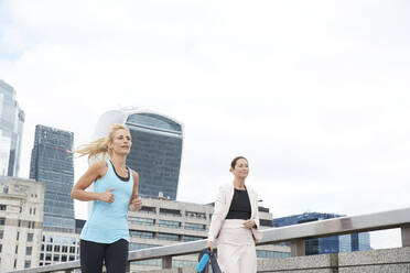 Woman jogging by businesswoman carrying bag on footbridge in city against clear sky - PMF01321