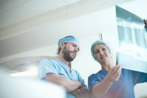 Male and female doctors discussing over medical x-ray image in hospital - AJOF00195