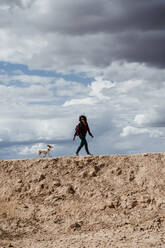 Spain, Navarre, Young woman hiking with dog in Bardenas Reales - EBBF00833