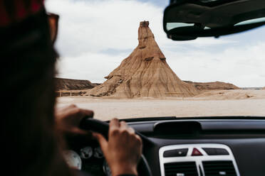 Spain, Navarre, Young woman driving car toward sandstone rock formation in Bardenas Reales - EBBF00836