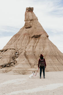 Spain, Navarre, Female backpacker standing with dog in front of sandstone rock formation in Bardenas Reales - EBBF00839