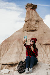 Spain, Navarre, Portrait of female tourist taking selfie in front of sandstone rock formation in Bardenas Reales - EBBF00848