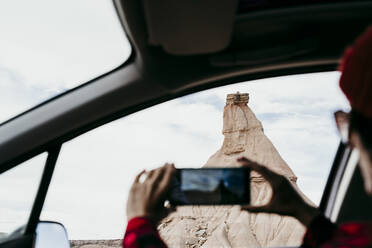 Spain, Navarre, Young woman sitting in car taking smart phone photos of sandstone rock formation in Bardenas Reales - EBBF00851