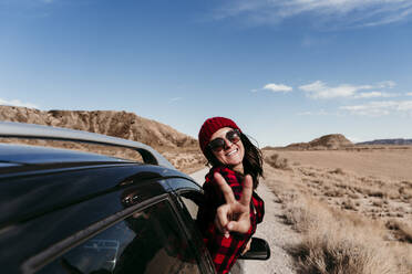 Spain, Navarre, Portrait of female tourist leaning out of car window making peace sign toward camera - EBBF00857