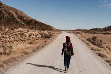 Spain, Navarre, Female tourist walking along empty dirt road in Bardenas Reales - EBBF00860