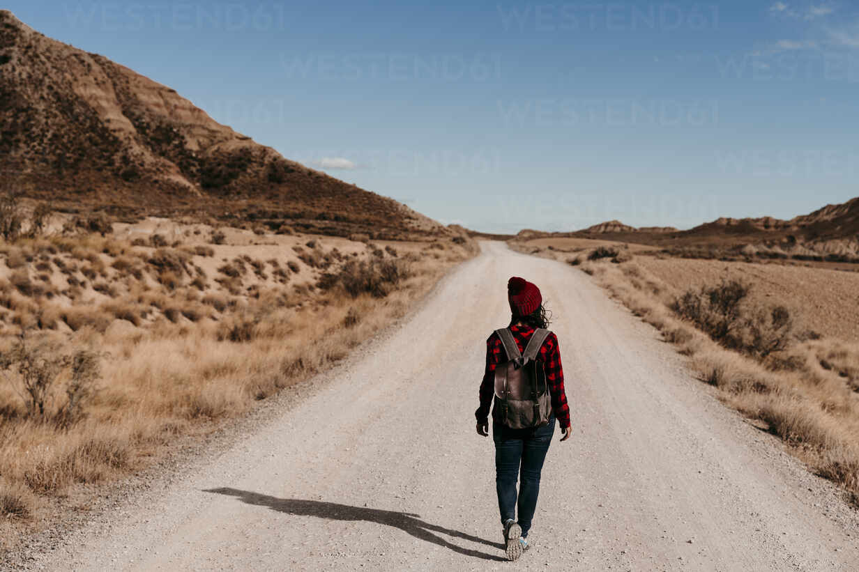 Spain, Navarre, Female tourist walking along empty dirt road in Bardenas Reales - EBBF00860 - Eva Blanco/Westend61