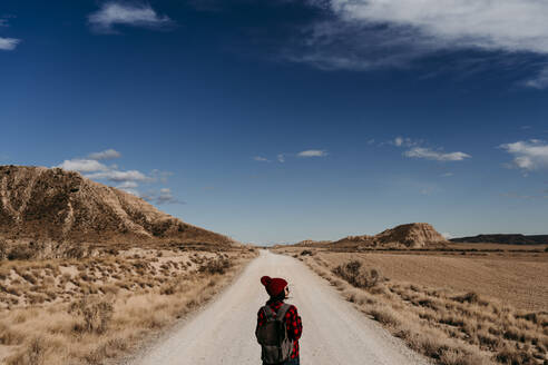 Spain, Navarre, Female tourist standing in middle of empty dirt road in Bardenas Reales - EBBF00863