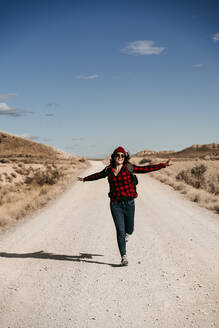 Spain, Navarre, Female tourist running toward camera along empty dirt road in Bardenas Reales - EBBF00866