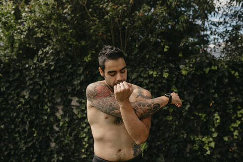Shirtless handsome man with tattoo stretching arm while doing warm up exercise against plants at back yard - DSIF00173