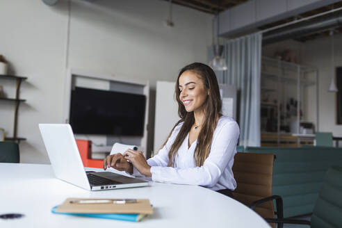 Smiling businesswoman using latptop at desk in office - DCRF00944