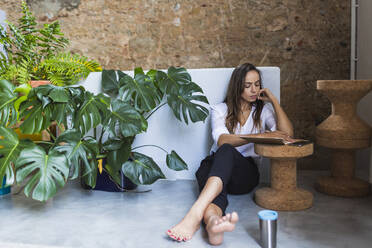 Businesswoman writing in diary while sitting on floor in office - DCRF00956