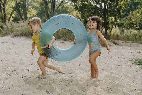 Children running with inflatable ring at beach - MFF06244