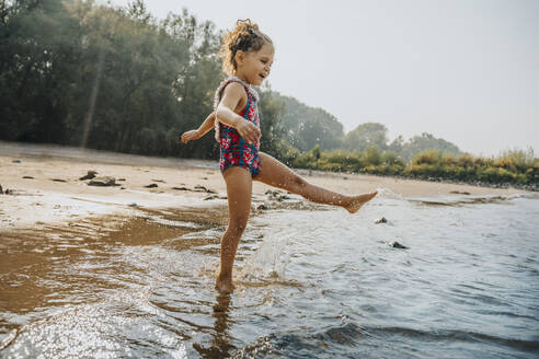 Cute little girl playing in water at beach on sunny day - MFF06253