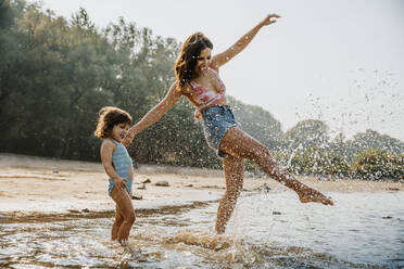 Mother and daughter enjoying in water at beach - MFF06256