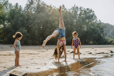 Daughters watching mother cartwheeling at beach - MFF06259