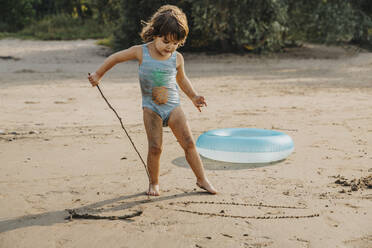 Cute girl drawing with stick on sand at beach - MFF06262