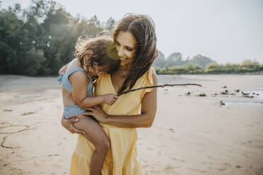 Happy mother holding daughter in arms at beach - MFF06283