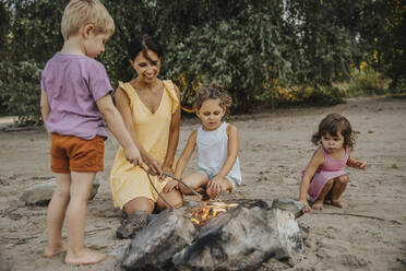 Mature woman and children making barbecue at beach - MFF06286