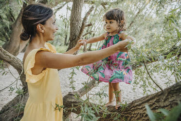 Mother helping daughter to stand on will tree branch - MFF06298