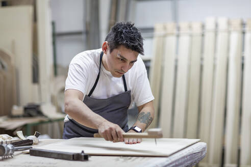 Artist giving design to wood through traditional method while standing at workshop - EIF00260