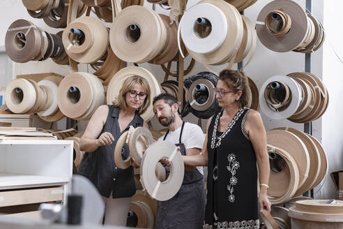 Interior designer and carpenter choosing spool while standing at workshop - EIF00281